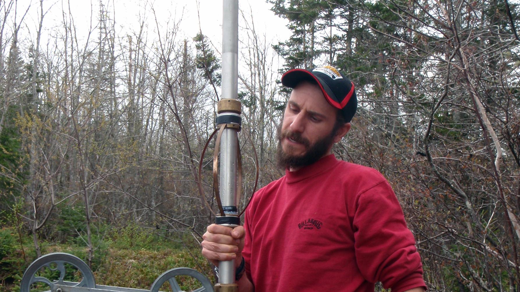 Technician handling geophysics probe in the field