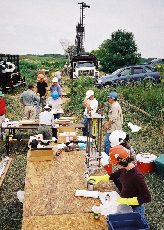 large group of researchers drilling and analyzing core at a remote field site